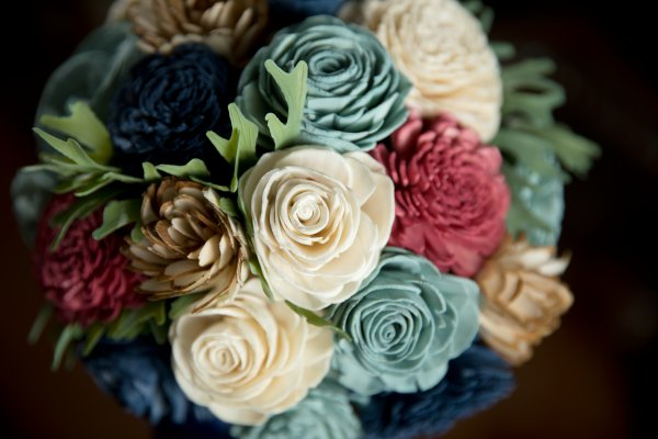 wood flower bridal bouquet featuring roses and greenery
