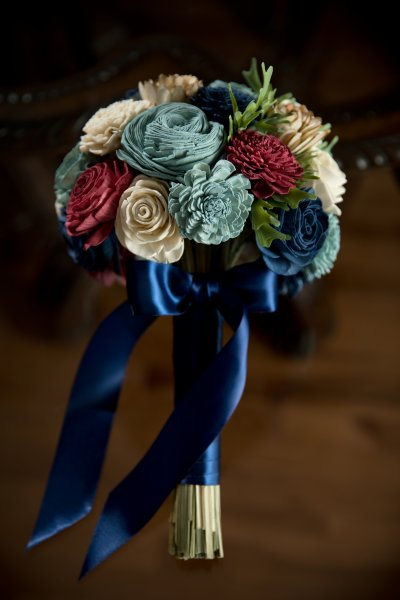wood flower wedding bouquet with light blue, navy, red, and white